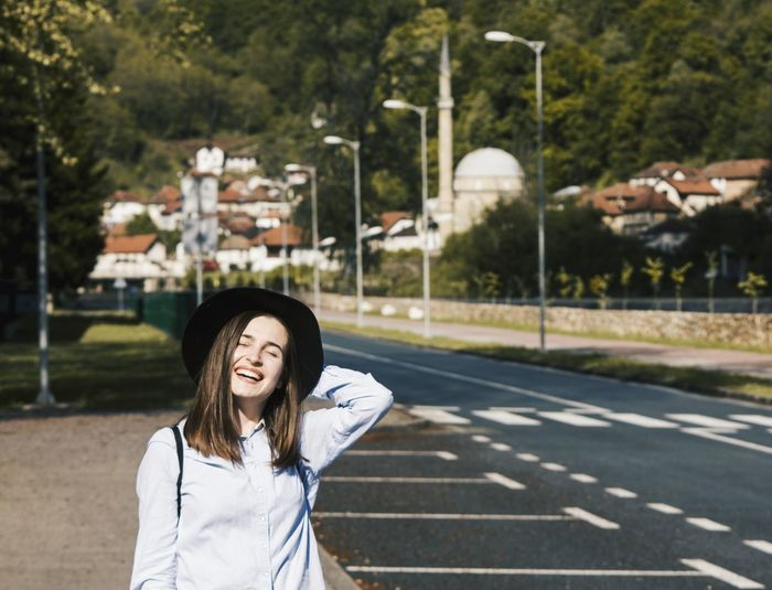 Smiling young woman wearing hat standing on road