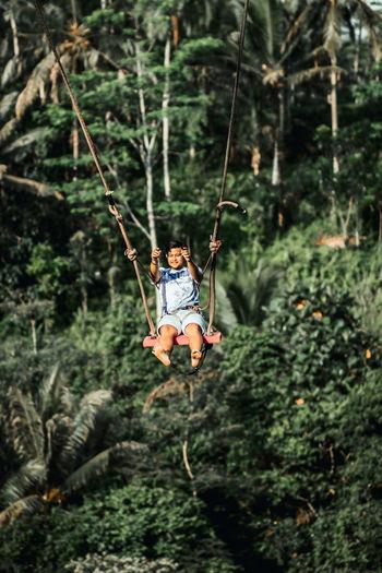 Boy on swing in forest