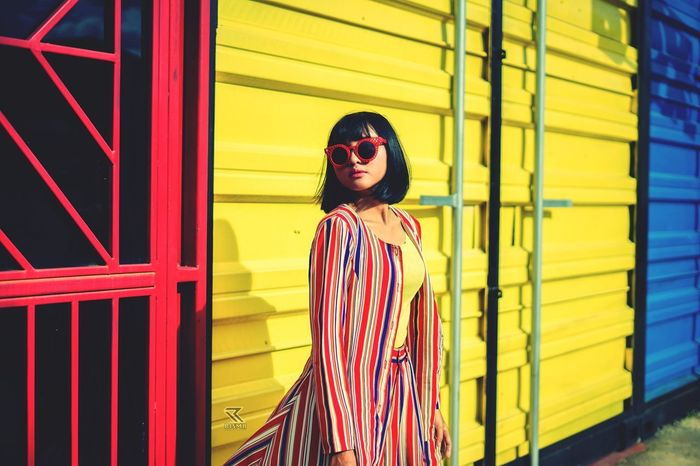 FULL LENGTH OF WOMAN STANDING ON YELLOW WALL