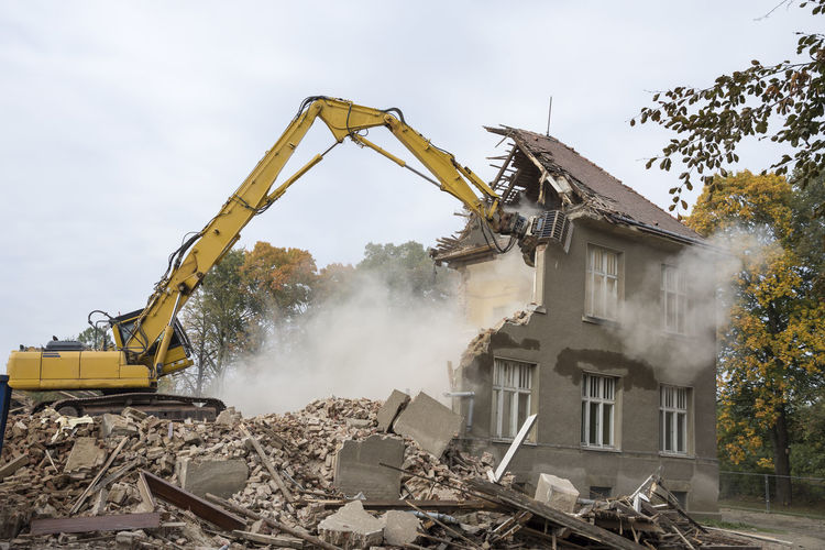 A digger demolishing houses for reconstruction. Built Structure Construction Machinery Construction Site Day Destruction Earth Mover Industry Machinery Outdoors People Rubble Sky