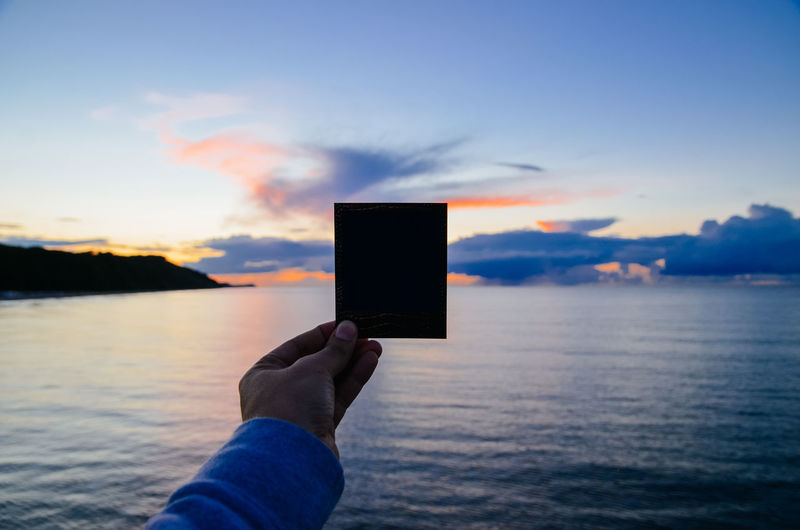 Cropped image of person holding instant film over sea against sky