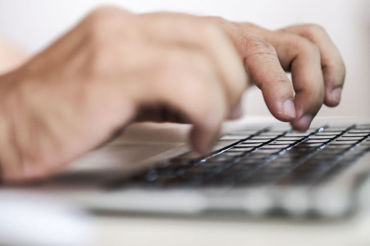 Cropped Hands Of Person Using Keyboard