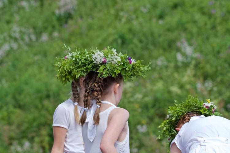 Young girls with midsummer-flower-garlands In Norway  Braids Childhood Day Dressed In White Flower Flowers Flowers Garland Flowers In Their Hair Focus On Foreground Girls Life Events Outdoors Togetherness Tree Young Adult