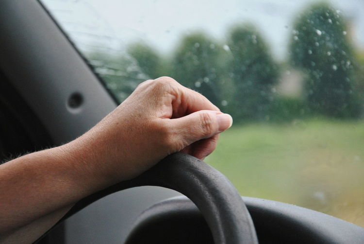 Cropped hand of person driving car