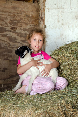 a little girl in pink overalls holds a young baby goat while they sit on straw in a barn on the family farm Adult Animal Themes Baby Goat Blond Hair Child Childhood Children Only Cute Domestic Animals Family Farm Full Length Girls Indoors  Looking At Camera One Animal One Girl Only People Pets Pink Color Pink Overal Portrait Sitting