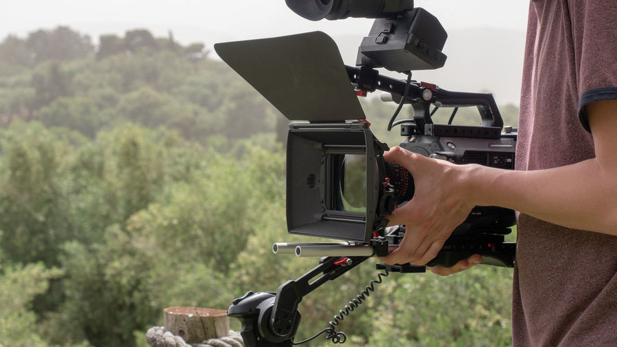 Midsection of photographer holding movie camera against trees