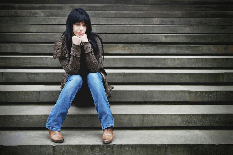 Full Length Of Thoughtful Young Woman Sitting With Hands On Chin On Steps