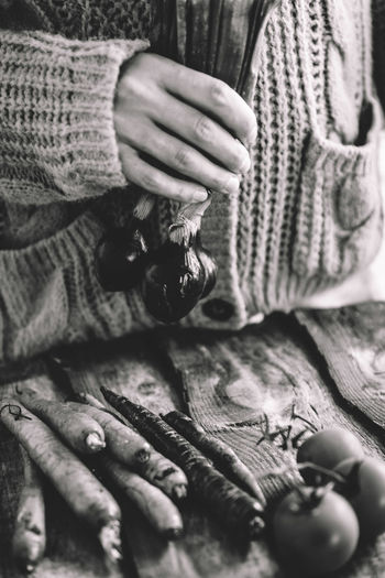 Adult Carrot Close-up Clothing Day Finger Front View Hand Holding Human Body Part Human Hand Lifestyles Men Midsection One Person Onion Real People Selective Focus Sweater Warm Clothing Winter Wood - Material