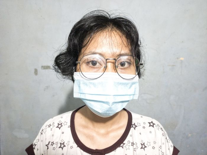 Portrait of woman wearing surgical mask and eyeglasses leaning against a wall