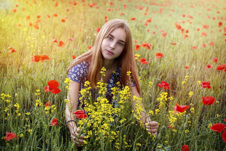 Full length of teenage girl in flower field