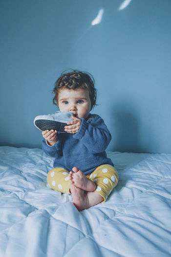 Cute boy holding toy while relaxing on bed