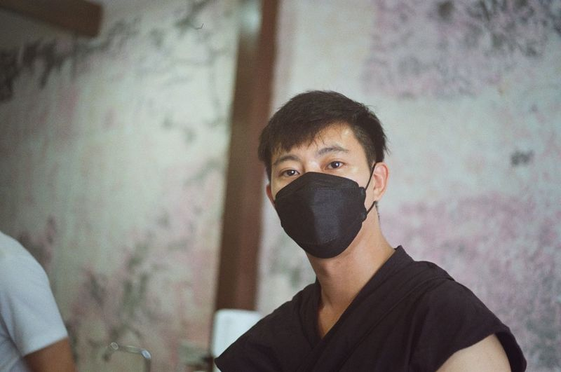 Portrait of young man covering face against wall