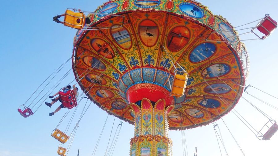 Low angle view of colorful chain swing ride spinning against sky