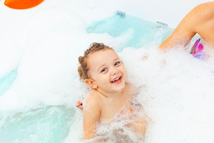 Smiling girl in bathtub