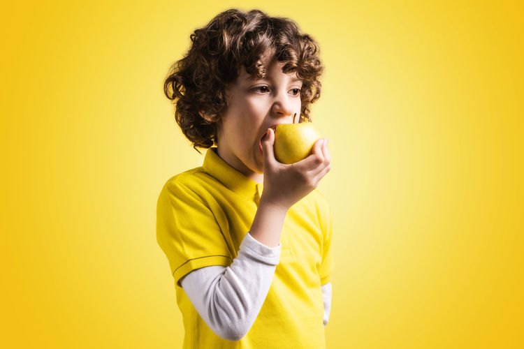 Young kid eating an apple fruit on a yellow background. Kid eating healthy food concept. Studio shot. Yellow Background Indoors  Portrait Holding Casual Clothing Waist Up Front View Hairstyle Mouth Open Fruit Concept Caucasian Kid Boy 7 Years Old Hair Healthy Eating Health Healthy Food And Drink Vivid Colors T Shirt Polo Shirt  Yellow Studio Shot Colored Background One Person Wellbeing Apple - Fruit Eating Food Biting Bite Teeth Freshness Backgrounds Colorful