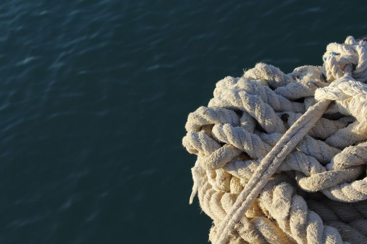 Close-Up Of Rope Tied To Sea