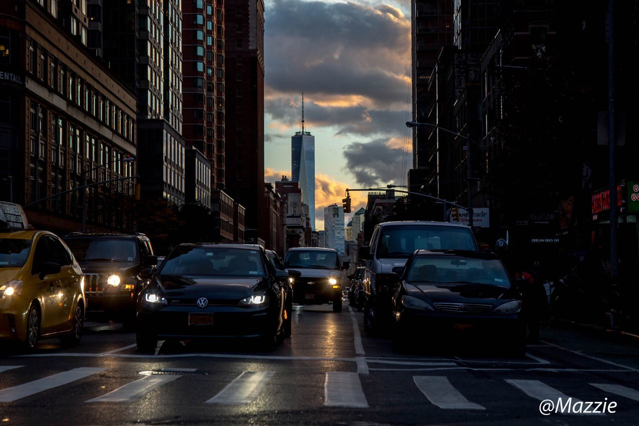 architecture, car, city, building exterior, built structure, land vehicle, transportation, street, sky, outdoors, road, cloud - sky, skyscraper, cityscape, no people, day