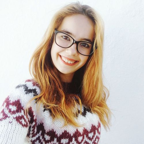 Portrait of smiling young woman wearing eyeglasses against wall