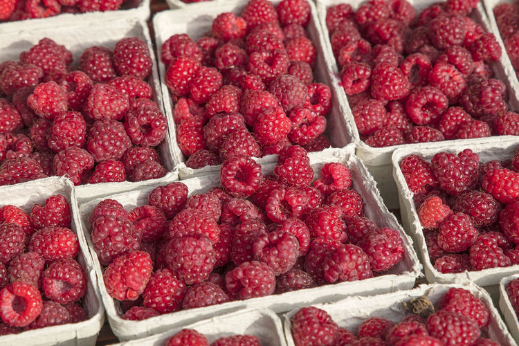 High angle view of raspberries in container for sale at market
