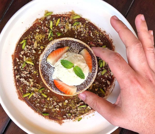 High angle view of hand holding bowl of soup