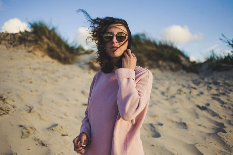 Young woman wearing sunglasses standing on beach
