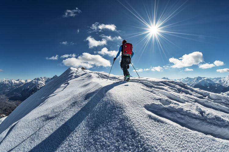 Man standing on snowcapped mountain against sky