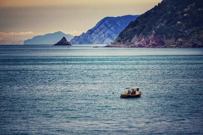 Scenic view of sea against mountain range with italian fisherman insidie his boat.