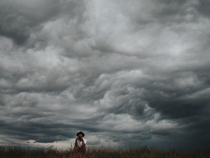 Photographer Crouching Against Cloudy Sky