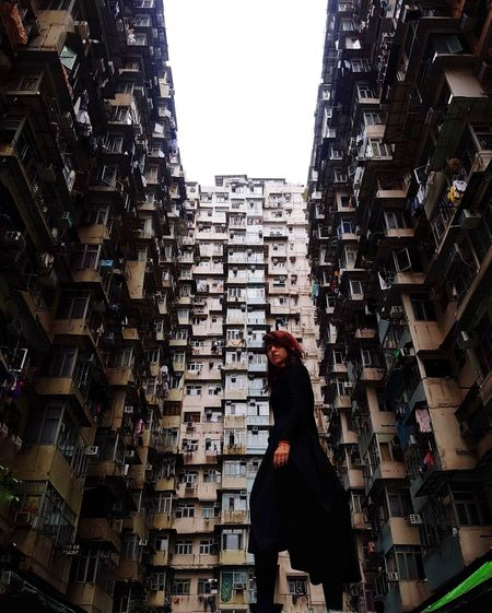 Side view of woman standing amidst buildings in city