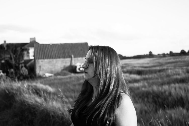 Side View Of Woman In Field Against Clear Sky