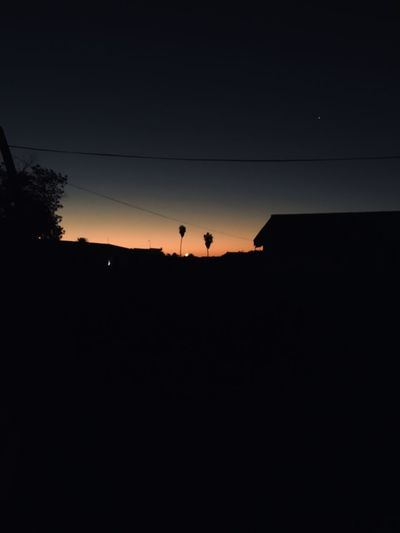 Silhouette landscape against clear sky during sunset