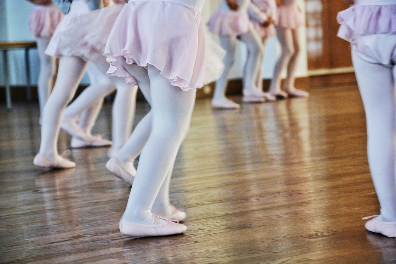 Low section of girls performing ballet on hardwood floor