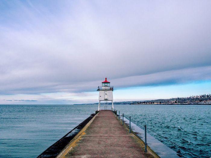 Footpath amidst sea leading towards lighthouse