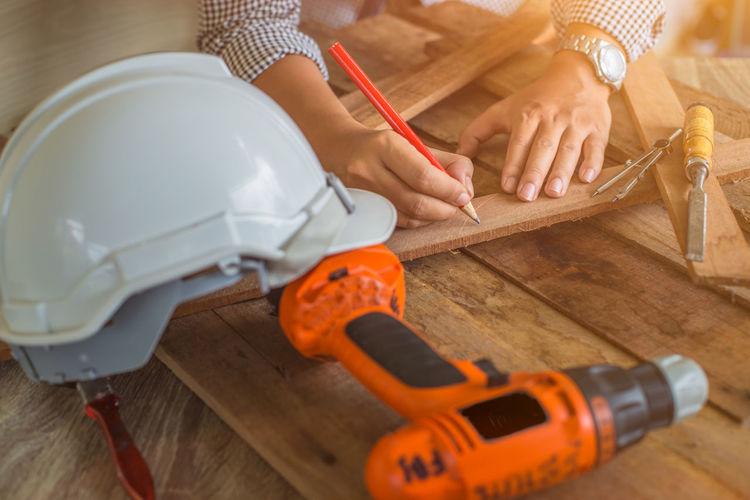Close-up of carpenter working in carpentry workshop