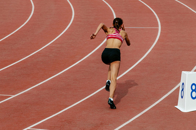 Girl runner athlete start of 400 meters race track and field competition