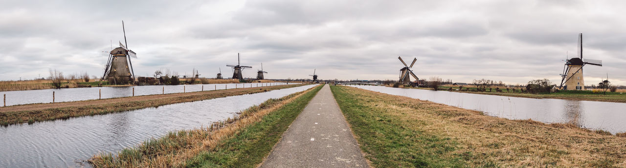 Panoramic view of road by canal against sky