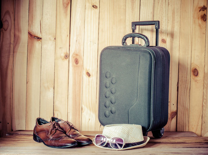 Leather shoes by hat and sunglasses with luggage against wooden wall