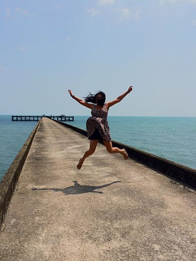 Woman with arms outstretched jumping on pier by sea against sky during sunny day