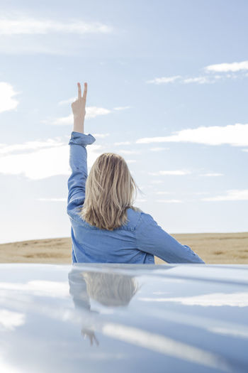 Rear View Of Woman Gesturing Peace Sign Against Sky