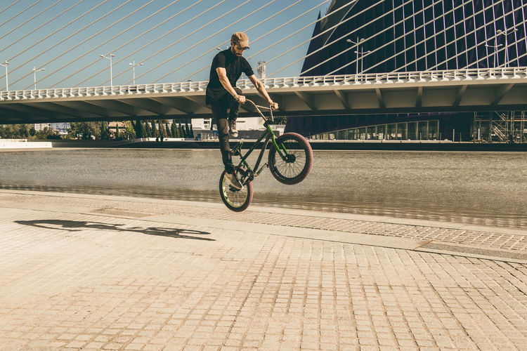 Man riding bmx cycle on footpath in city