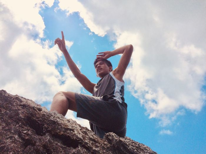 Low angle view of man standing on rock against blue sky