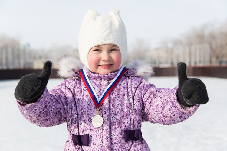 Portrait of smiling girl showing thumbs up while wearing medal standing against snow during winter