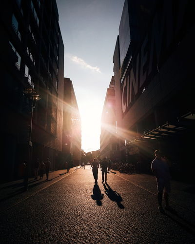Silhouette people walking on street in city during sunset