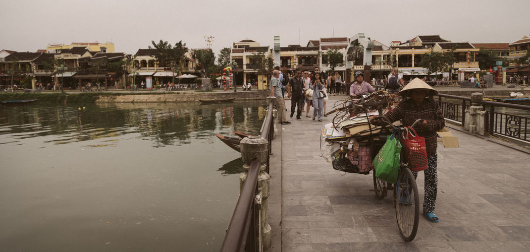 Sales woman on bridge in Hoi An, Vietnam Adult Architecture Bicycle Building Exterior Built Structure City Day Full Length Group Of People Land Vehicle Large Group Of People Leisure Activity Lifestyles Mammal Men Mode Of Transport Nature Outdoors People Real People Sky Togetherness Transportation Water Women