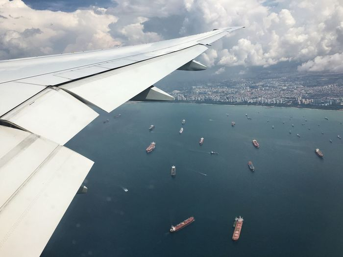 Marine vessels are seen from the air as a Boeing 77-300ER takes off from Singapore Changi International Airport Aerial View Aircraft Wing Beauty In Nature Boat City Cloud Cloud - Sky Cloudy Cropped Day Flying Journey Mid-air Mode Of Transport Nature Nautical Vessel No People Outdoors Part Of Sailboat Scenics Sky Transportation