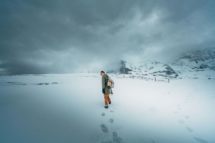 Man walking on snowy land against cloudy sky