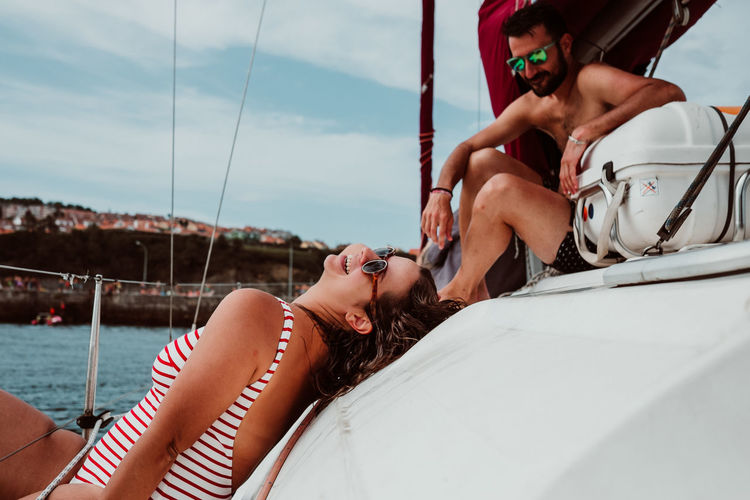 Midsection of woman relaxing on boat sailing in sea