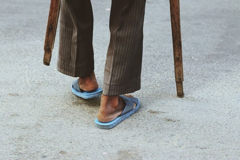 Low section of disabled man walking with crutches on street