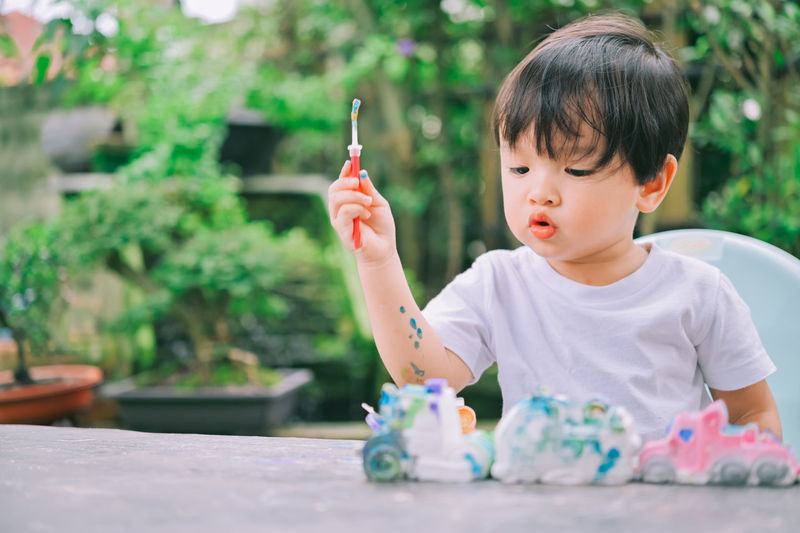 Cute boy holding toy while sitting outdoors