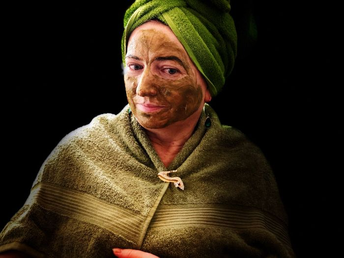 Portrait of woman with facial mask against black background
